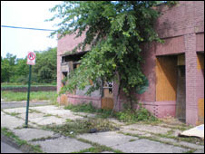 Derelict building overgrown with weeds and vegetation in Detroit