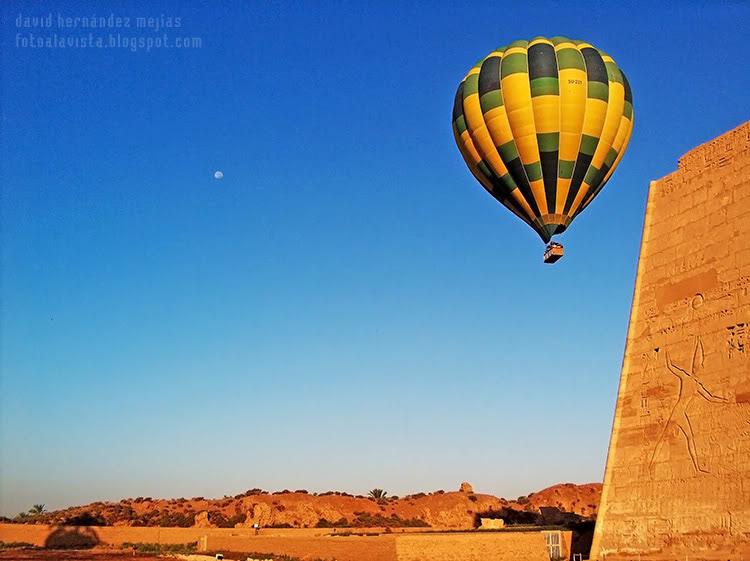 Un globo aerostático se eleva en el cielo del desierto de Egipto, muy cerca de un templo con el relieve de un faraón en la fachada, al que parece que se le ha escapado el globo de la mano o que está señalándolo