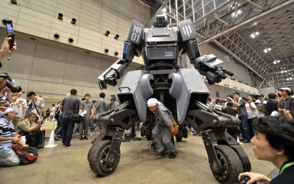 """CORRECTION: NAME Engineer Kogoro Kurata ...CORRECTION: NAME Engineer Kogoro Kurata (C) walks in front of Japanese electronics company Suidobashi Heavy Industry's newly unveiled robot """"Kuratas"""" at the Wonder Festival in Chiba, suburban Tokyo on July 29, 2012. The Kuratas robot, which will go on sale with a price tag of one million USD ,measures four meters in height, weighs four tons and has four wheeled legs that can either be controlled remotely through the 3G network or by a human seated within the cockpit.  AFP PHOTO / Yoshikazu TSUNOYOSHIKAZU TSUNO/AFP/GettyImages"""