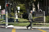 A police official walks past the Maplewood Apartments after a shooting in Lakeside, Calif. Tuesday, Sept. 25, 2012. The San Diego County sheriff's Capt. Duncan Fraser said two deputies and a suspect have been shot while the deputies were trying to contact a child abuse suspect at the suburban apartment complex. (AP Photo/Gregory Bull)