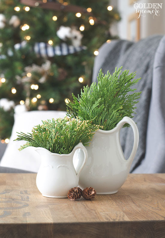Simple display for Christmas....white pitchers filled with greenery | Friday Christmas Favorites at www.andersonandgrant.com