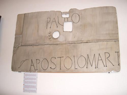 """Reproducción de la lápida hallada en la tumba, con la inscripción PAVLO APOSTOLO MART (""""Pablo, apóstol mártir""""). Basílica de San Pablo Extramuros, Roma (Italia)."""