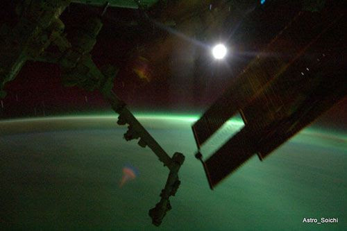 The ISS flies over an aurora while orbiting the dark side of the Earth, on April 6, 2010.  The Moon looms in the background.
