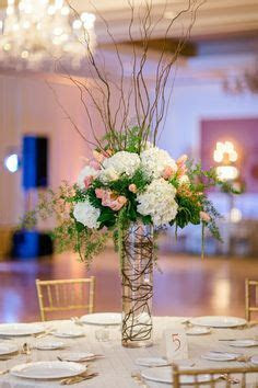 Tall arrangements in clear glass vases created using white
