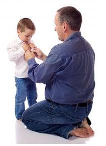 Foto: hombre ayudando a un niño a abotonarse una camisa
