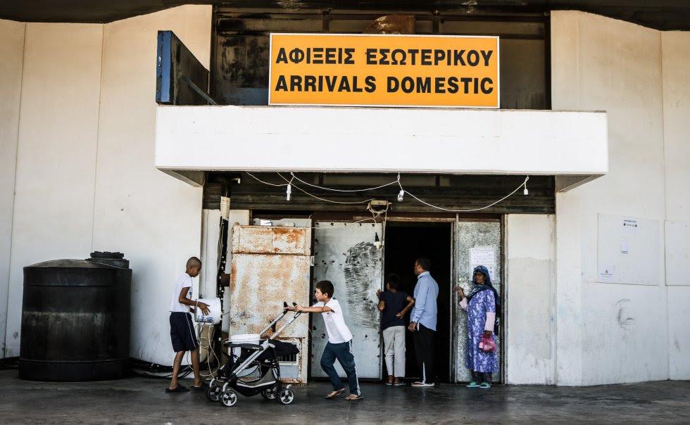 El campo de Elliniko, apenas unos kilómetros a las afueras de Atenas, se extiende a lo largo de un complejo de viejos edificios aeroportuarios y de las instalaciones abandonadas que fueron construidas para los Juegos Olímpicos de 2004. Espacios que una vez acogieron partidos de hockey y béisbol ahora alojan a unos 3.000 migrantes procedentes de Afganistán, Siria y un poco de todas partes. Según las últimas estimaciones oficiales, son exactamente 2.849. La zona de llegadas acoge actualmente a un millar de personas refugiadas. Se estima que tiene capacidad para 1.400