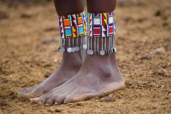 Africa | Masai Mara tribes woman with beads on legs.  Photo by Darrell Gulin. (http://www.gulinphoto.com)