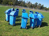 12 blue rubbish bins arranged in a circle.