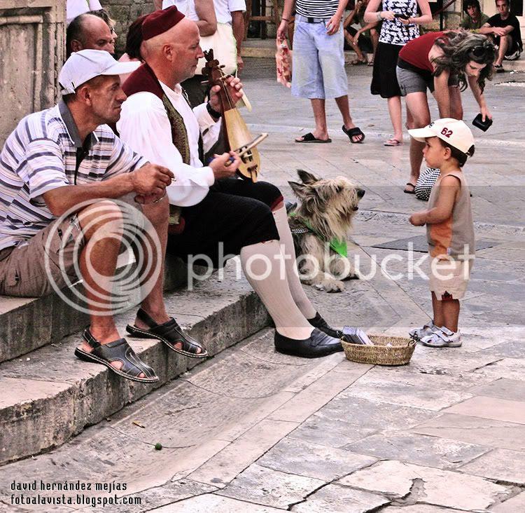 Un músico tradicional toca al lado de un perro y de otro hombre mientras un niño observa