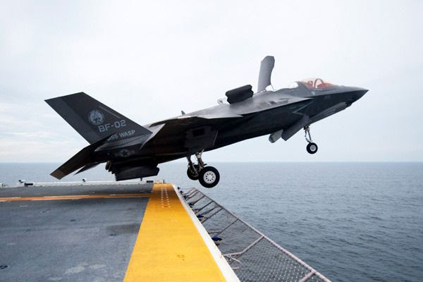 An F-35B Lightning II fighter jet takes off from an L-Class aircraft carrier at sea.