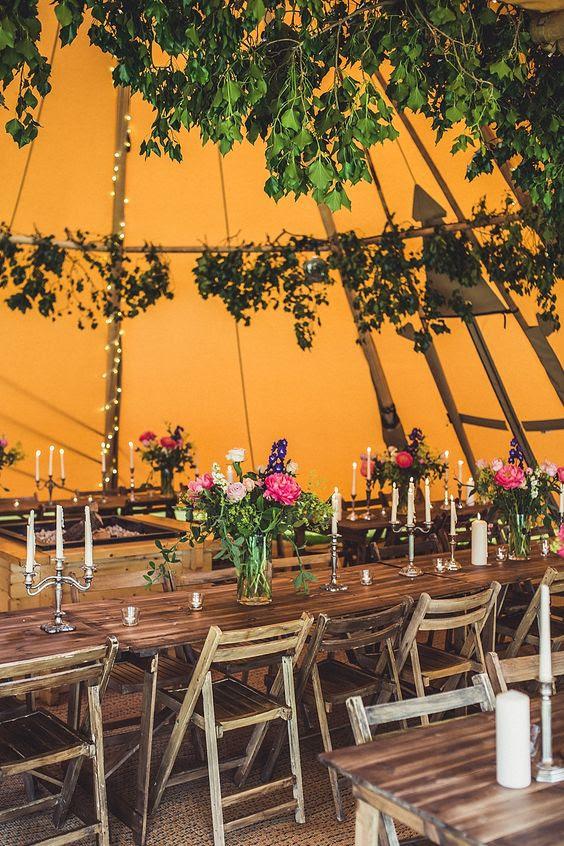 einem kräftigen orange Zelt mit grün-und Kräuter, Lichter und Kerzen für eine Herbst-Wald-Hochzeit