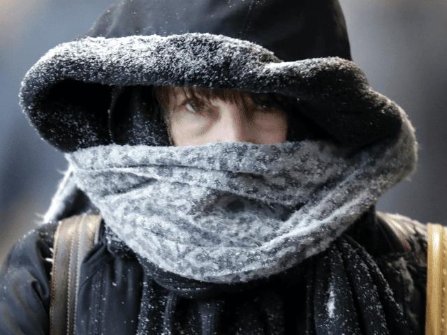 Un viajero se dirige a la estación de tren de cara a temperaturas que caen rápidamente y al comienzo de una tormenta de nieve durante su viaje a casa a los suburbios del sur el lunes 5 de febrero de 2018 en Chicago.  (AP Photo / Charles Rex Arbogast)