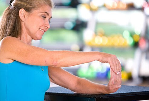 Woman demonstrating wrist flexion and extension exercise.