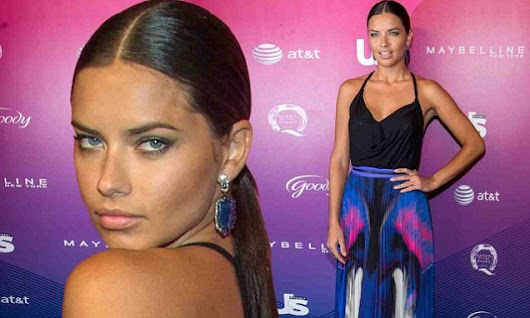 Adriana Lima displays figure in black top and eye-catching maxi skirt