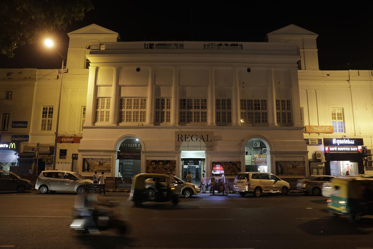 In this Thursday, March 30, 2017 photo, motorists drive past the colonial era Regal Theater in New Delhi, India. The Indian capital's iconic theater signed off on Thursday night after more than eight decades with nearly 600 movie buffs cheering a 1964 Bollywood classic at a final screening. With nostalgic theater-goers singing their way to the exits, the iconic New Delhi theater has closed its doors to make way for a multiplex.