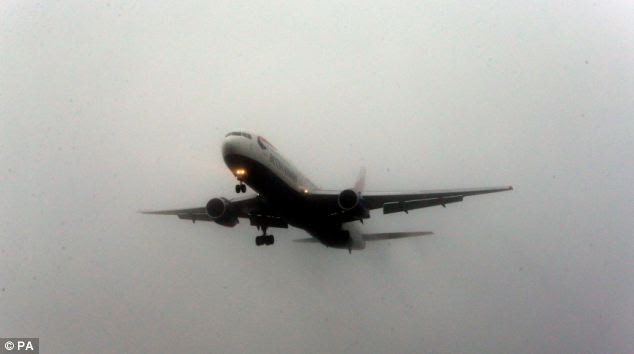 A plane prepares to lands in fog at Heathrow Airport which was disrupted by delays this morning