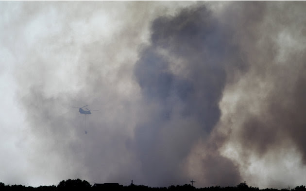 A helicopter moves in to drop water on a wildfire at Possum Kingdom Lake, Texas, Wednesday, Aug. 31, 2011, the day after it swept through the neighborhood and destroyed 25 homes. (AP Photo/LM Otero)