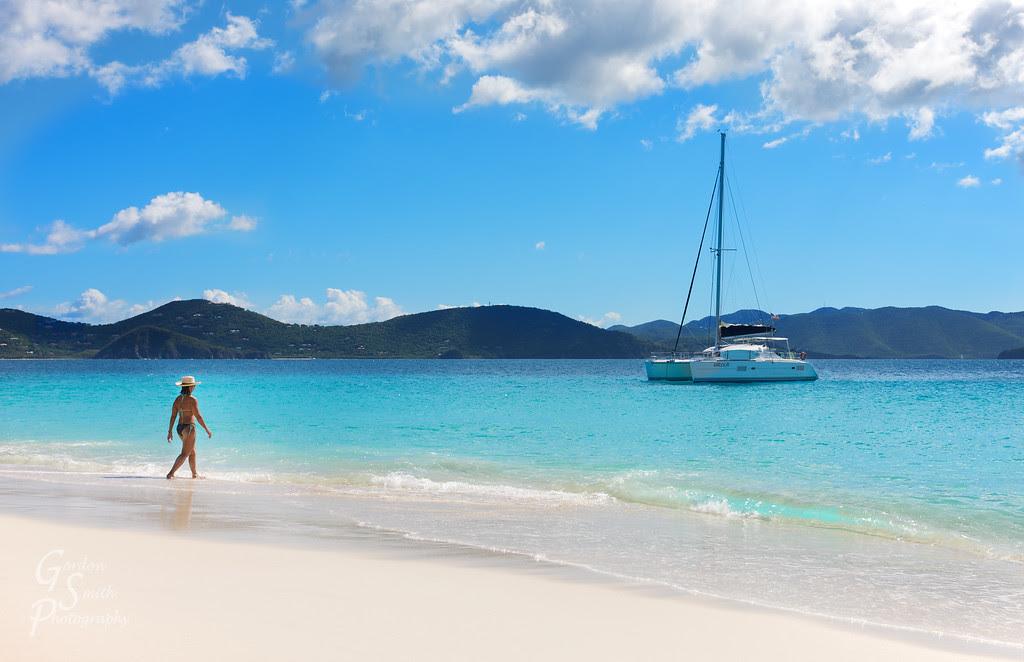 bikini-clad woman and sailboat Sandy Cay, BVI