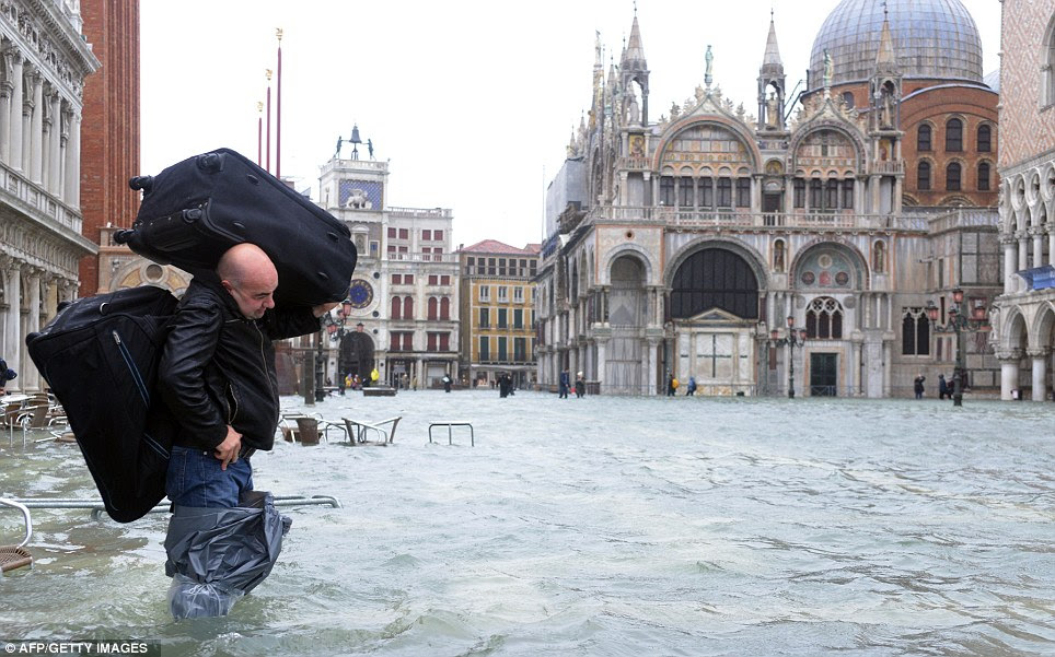 Wearing plastic bags to cover his legs, a tourist carries two suitcases in flooded waters