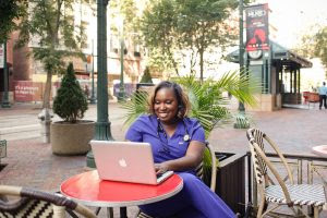 Dr, Kimberly Brown working on a laptop at a cafe