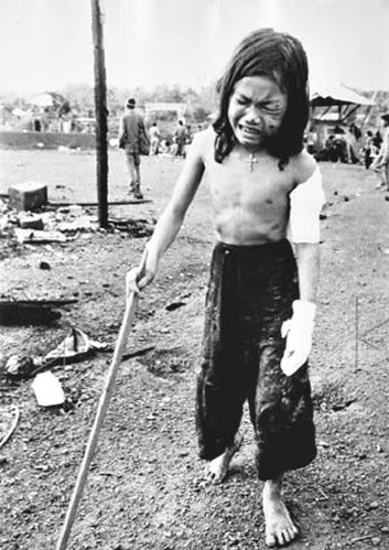 12-yr-old girl with a cross around her neck and w. multiple wounds uses a stick to hobble through debris in Dong Xoai as she attempts to get to an evac helicopter. Her father, sister and a brother were killed and their home destroyed, by Horst Faas 1965