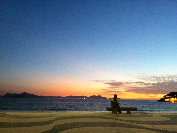 Amanhecer no Posto 6, em Copacabana, atrás da estátua de Drummond (Foto: José Raphael Berrêdo/G1)