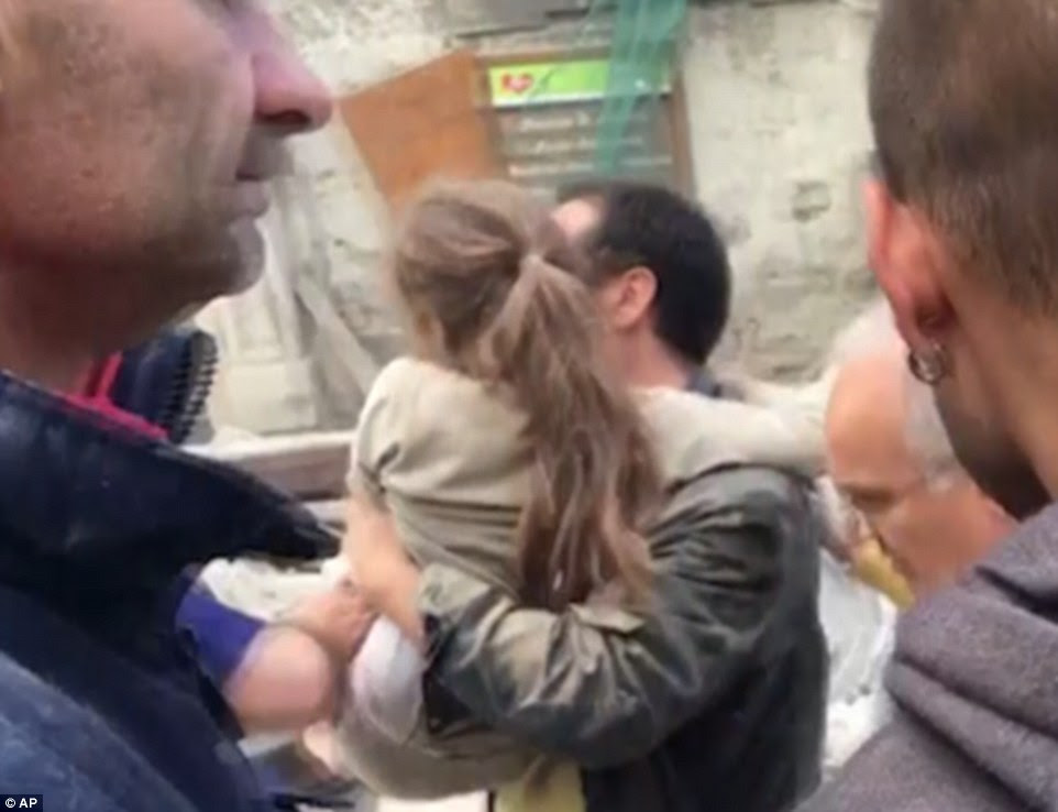 A video has emerged of a young girl covered in dust being carried to safety after she was pulled from the rubble in Amatrice