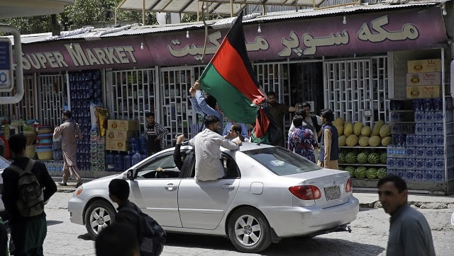 Afghans wave a black, red and green banner in honor of the Afghan flag — a banner that is becoming a symbol of defiance since the Taliban have their own flag. AP