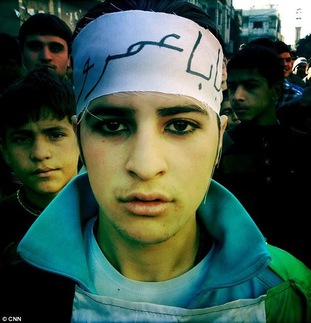 Rebeldes: Um adolescente, com os olhos de espessura com kohl, reúne para uma demonstração sexta-feira no distrito de Baba Amr