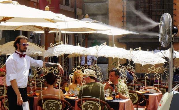 En un restaurante romano, el ventilador rocía agua para refrescar a los comensales
