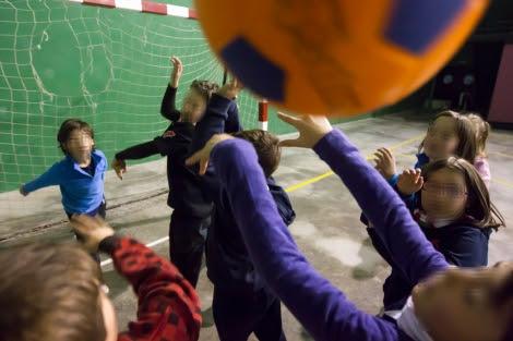 Varios niños juegan a la pelota en un polideportivo.  Iñaki Andrés