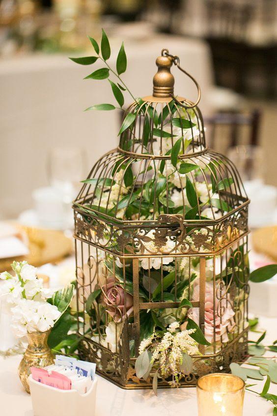 einen metallischen Käfig mit laub und üppigen Blumen für eine schöne Hochzeit Herzstück
