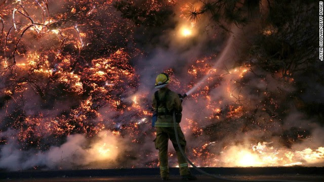 A firefighter douses flames of the Rim Fire in Groveland, California, near Yosemite National Park, on Saturday, August 24. The fire had consumed nearly 126,000 acres as of Saturday and has moved into a remote area of the park.