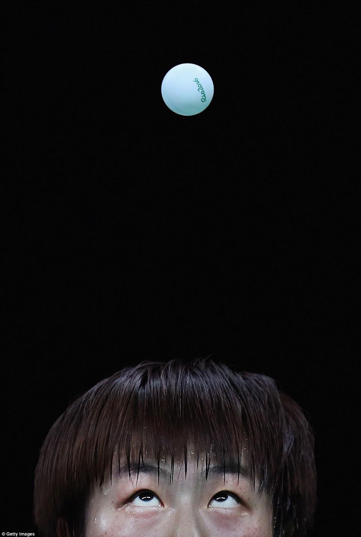 Ning Ding, que iria ganhar o ouro em ambos os simples e duplas de ténis de mesa para a China, observa a bola de perto