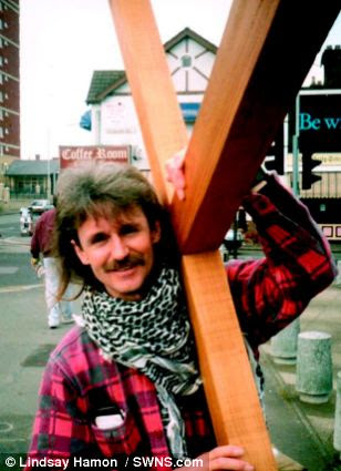 Challenge: He is seen here carrying the cross in Walthamstow, east London during the earlier stages of his journey