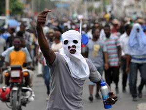 22/01 - Manifestantes marcham durante um protesto contra as eleições presidenciais em Porto Príncipe, no Haiti.  A autoridade eleitoral do país adiou o segundo turno das eleições que aconteceria neste domingo (24) após protestos e acusações de fraude (Foto: Hector Retamal/AFP)