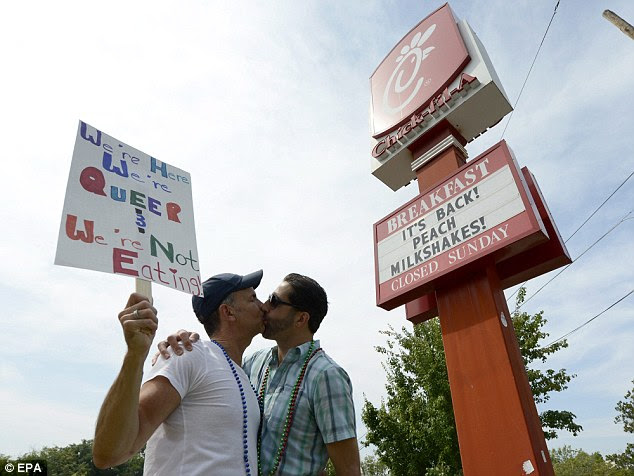 Message: Gay couple Jim Fortier, left, and Mark Toomajian kiss each other during a gay and lesbian kiss in protest outside a Chick-fil-A restaurant in Decatur, Georgia