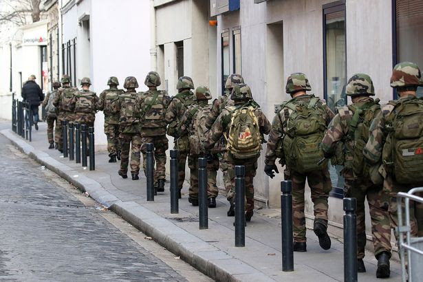 Soldiers are seen patrolling a street of Saint Denis on November 18, 2015 in Saint-Denis, France.