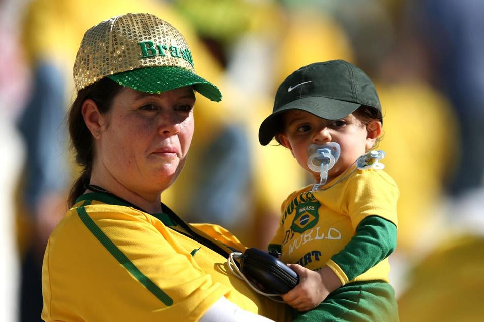 A fan held a child before the opening ceremony of the 2014 FIFA World Cup Brazil.