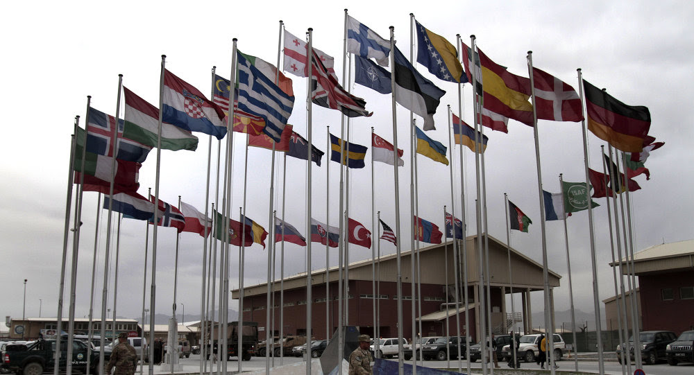 NATO Soldiers walk under country member flags at a NATO base at Kabul International Airport in Kabul, Afghanistan