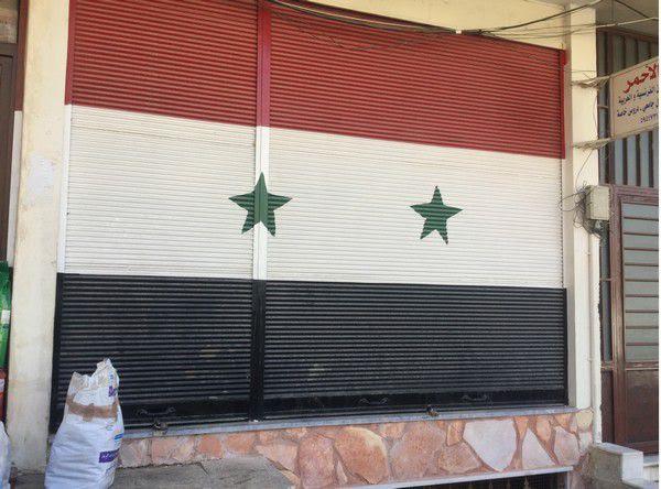 Peint sur les fermetures des échoppes, le drapeau syrien est omniprésent