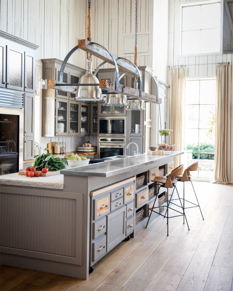 """Ronnie enlisted Nashville designer Rachel Halvorson to add a layer of refinement to the rustic home. First up: the kitchen, where an abundance of moody gray cabinetry, limestone countertops, and stainless steel appliances add luxe elements to the rough-hewn space. There, Rachel also introduced a key part of her design for the house: light fixtures that up the wow factor in each room. Starting with three 16"""" polished nickel pendants, she designed a custom pulley framework for them using barnwood and steel. The final product is a sleek showpiece that can hold its own above the 13-foot-long kitchen island. In this photo: To maximize storage, one half of the island contains a series of baskets and bins; the other half has an additional work surface mounted with coasters to roll away when not in use."""