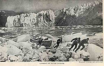 Six men pulling a boat on to an icy shore, with a line of ice cliffs in the background