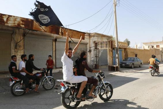 A resident of Tabqa city touring the streets on a motorcycle waves an Islamist flag in celebration after Islamic State militants took over Tabqa air base, in nearby Raqqa city August 24, 2014. REUTERS-Stringer
