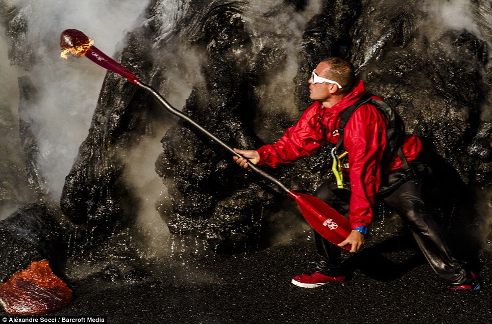 Steaming: Daredevil Pedro Oliva runs with his oar on fire after molten lava set fire to it during a kayak