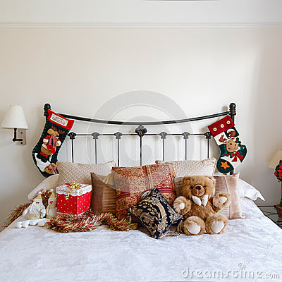 Cozy bedroom with Christmas decorations and stockings.