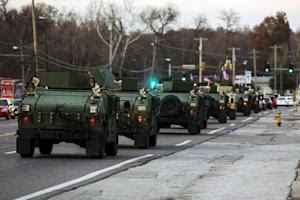File photo of National Guard vehicles driving down …