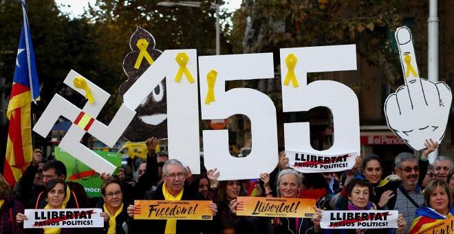 Varias personas con carteles contra la aplicación del artículo 155 de la Constitución, en la manifestacin para pedir la libertad de los líderes de ANC y Ômnium Cultural, Jordi Sánchez y Jordi Cuixart. REUTERS/Javier Barbancho