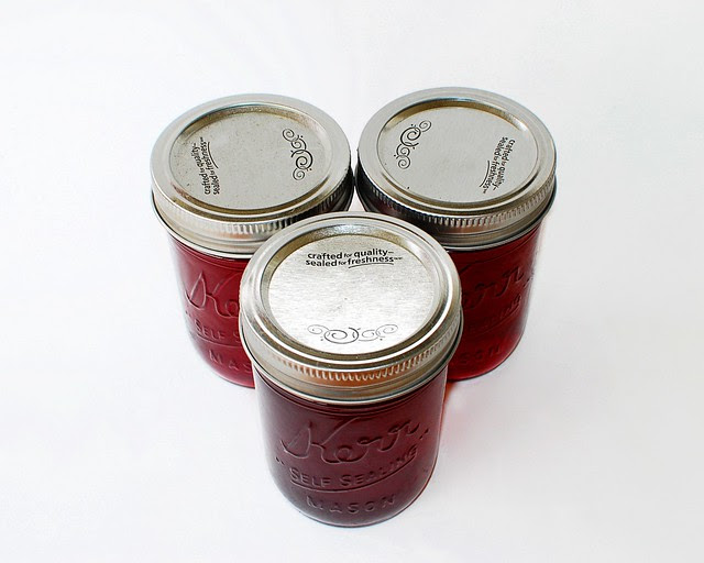 Three jars of red jelly.