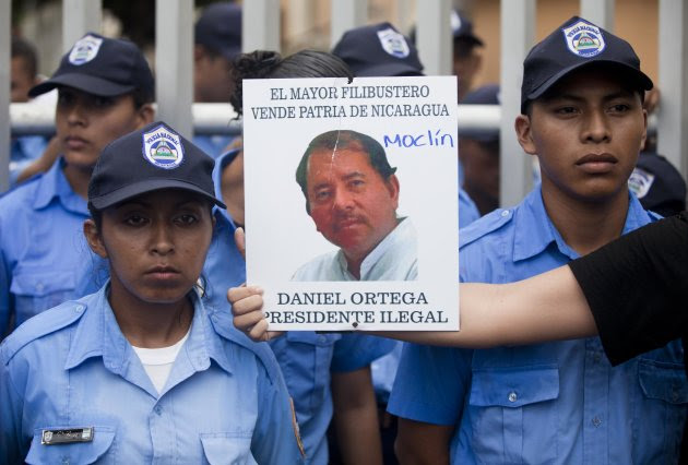 """<p> A demonstrator holds out a picture of Nicaragua's President Daniel Ortega that reads in Spanish """"The biggest thief and traitor of Nicaragua, Daniel Ortega illegal President"""" in front of a line of police during a protest against a canal project outside the National Assembly in Managua, Nicaragua, Thursday, June 13, 2013. A multi-billion dollar proposal to plow a massive rival to the Panama Canal across the middle of Nicaragua was approved by the National Assembly Thursday, capping a lightning-fast approval process that has provoked deep skepticism among shipping experts and concern among environmentalists. (AP Photo/Esteban Felix)"""